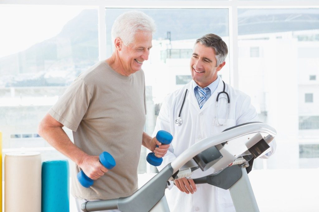 old guy running on the treadmill and doctor